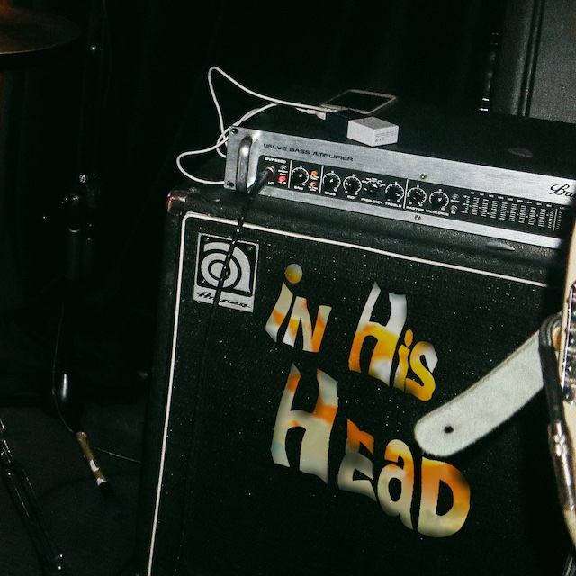 "Single cover for ""In His Head"", displaying a dark room with an amp with ""In His Head"" pasted over it"